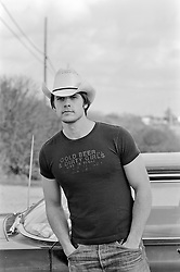 handsome cowboy leaning against a car