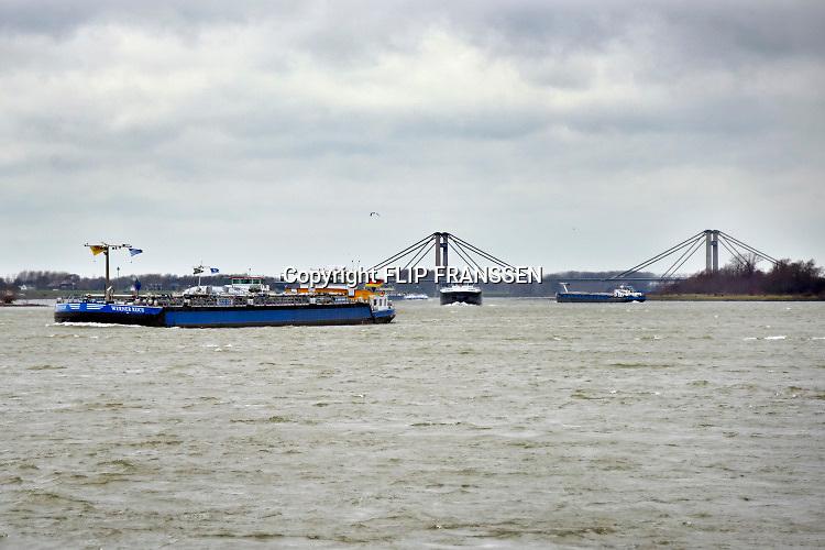 Nederland, Dodewaard, 8-2-2019 Een binnenvaartschip vaart over de Waal .  Op de achtergrond de prins willem-alexanderbrug bij Tiel .Foto: Flip Franssen