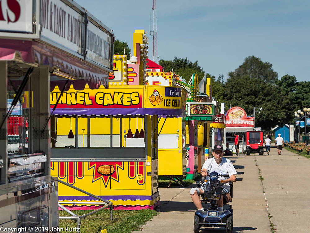 30 JULY 2019 - DES MOINES, IOWA:  A man rides his scooter past closed concession stands on the Iowa State Fair fairgrounds. The Iowa State Fair Is one of the largest state fairs in the United States and runs for 10 days. In 2019, it runs from August 8 to 18. More than one million people attend the fair every year. Most of the food concessions at the fair don't open until August 3, when exhibitors arrive, but the Westmoreland Concessions corn dog stand opened on July 28. One of the stand's workers said a lot of people drive out to the fairgrounds the week before the fair to buy corn dogs because the fair is so crowded and concession lines are very long.   PHOTO BY JACK KURTZ