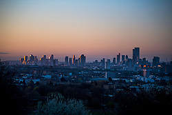 © Licensed to London News Pictures. 11/04/2021. London, UK. The rising sun reflects off the financial district of the city of London, as seen from Hampstead Heath in North London, on a cold, spring morning. Large parts of the UK are waking to freezing temperatures and snow. Photo credit: Ben Cawthra/LNP