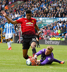 Manchester United's Marcus Rashford and Huddersfield Town goalkeeper Jonas Lossl battle for the ball during the Premier League match at the John Smith's Stadium, Huddersfield.