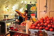 Israel, Jerusalem Man squeezes fresh pomegranate juice at a stall in the market.
