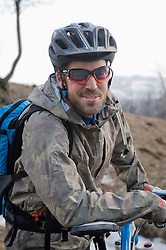 Mid adult man with mountain bike, smiling, Italy