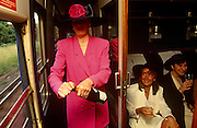 Girlfriends eagerly await the opening by one woman of a bottle of bubbly, en-route by train to Ascot racecourse  on Ladies Day at Royal Ascot racing week. The hats are wide-brimmed and the pinks are bright in this first class carriage with an old fashioned corridor. Royal Ascot is held every June and is one of the main dates on the sporting calendar and English social season. Over 300,000 people make the annual visit to Berkshire during Royal Ascot week, making this Europe's best-attended race meeting. There are sixteen group races on offer, with at least one Group One event on each of the five days. The Gold Cup is on Ladies' Day on the Thursday. There is over £3 million of prize money on offer.