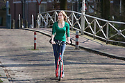 Een meisje rijdt op een step door Utrecht