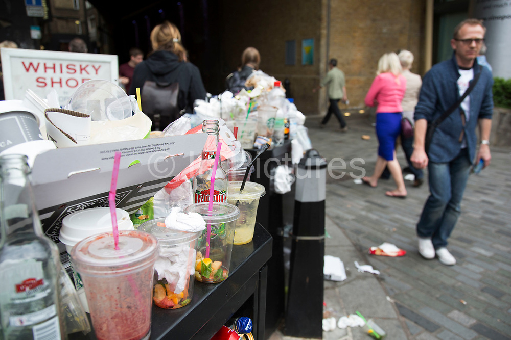 Overflowing bin and litter at Blackfriars, London, UK. At certain times, especially weekends and public holidays, the volume of people in the area generates a big problem with trash. Rubbish piles high in certain places and proves unsightly for such an important area of London.