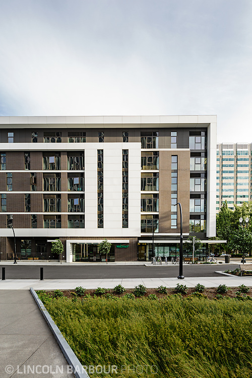 A large apartment building with big modern, geometric design elements seen from across the street.  Well maintained landscaping sits in the foreground.