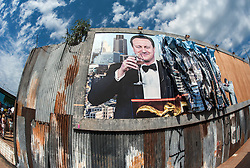 © Licensed to London News Pictures. 22/08/2015. Weston-super-Mare, North Somerset, UK.  A billboard of David Cameron being crumpled by a figure on the first main day of BANKSY's Dismaland show at the old Tropicana on Weston seafront, when the event is open to the general public. Photo credit : Simon Chapman/LNP