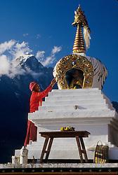 Asia, Nepal, Himalayas, Solu Khumbu region, Lukla. Monk painting new stupa (Buddhist shrine) at entrance to village.