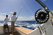 Fly angler and crew teasing fish behind boat before presenting the fly.