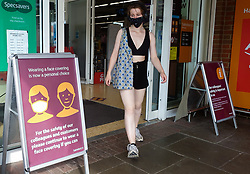 © Licensed to London News Pictures. 19/07/2021. London, UK. A shopper wearing a face covering walks past 'Wearing a face covering is now a personal choice' poster displayed outside a Sainsbury's superstore in north London. Sainsbury's superstore in north London. The Covid-19 measure of wearing face coverings is no longer mandatory as the legal requirement ends today, Freedom Day. The government recommends that people continue to wear a face covering in crowded and enclosed spaces. Shoppers shopping in Sainsbury's will need to carry on wearing face coverings.  Photo credit: Dinendra Haria/LNP