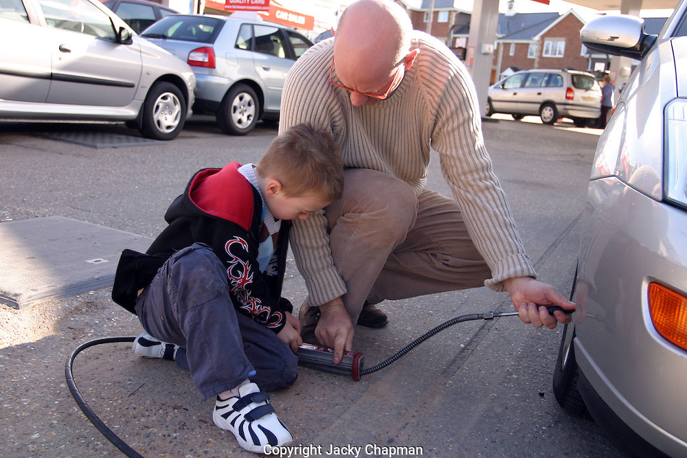 Father showing son how to blow up car tyre and check wheel pressure
