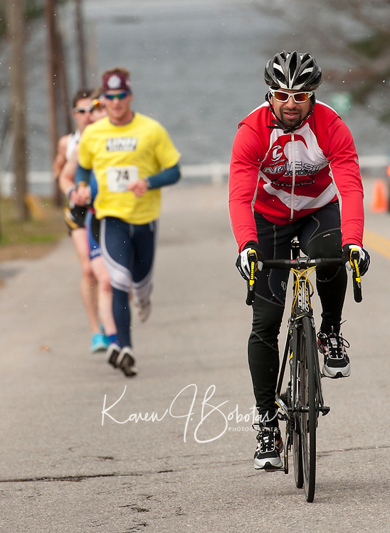 With snowflakes starting to fall Alex Indeck peddles ahead of the lead runners during the Frozen 5K on Saturday morning to benefit the WLNH Children's Auction.   (Karen Bobotas/for the Laconia Daily Sun)