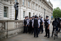 """© Licensed to London News Pictures. 03/06/2020. London, UK. Police officers line up next to Downing Street as  a """"Justice for Black Lives"""" demonstration passes by. Protests have taken place across the United States and in cities around the world in response to the killing of George Floyd by police officers in Minneapolis on 25 May. Photo credit: Rob Pinney/LNP"""