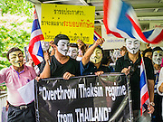 """02 JUNE 2013 - BANGKOK, THAILAND: Anti-government protesters march through the Skywalk system in Bangkok. The so called White Mask protesters are strong supporters of the Thai monarchy.  About 300 people wearing the Guy Fawkes mask popularized by the movie """"V for Vendetta"""" and Anonymous, the hackers' group, marched through central Bangkok Sunday demanding the resignation of Prime Minister Yingluck Shinawatra. They claim that Yingluck is acting as a puppet for her brother, former Prime Minister Thaksin Shinawatra, who was deposed by a military coup in 2006 and now lives in exile in Dubai.     PHOTO BY JACK KURTZ"""