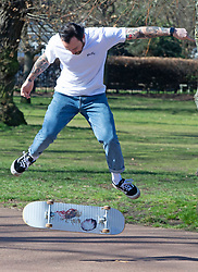 © Licensed to London News Pictures 09/03/2021. Greenwich, UK. A skateboarder doing tricks. People out and about during a third national Coronavirus lockdown and making the most of the sunny weather in Greenwich Park, London. The Met Office has predicted two days of strong winds and rain this week. Photo credit:Grant Falvey/LNP