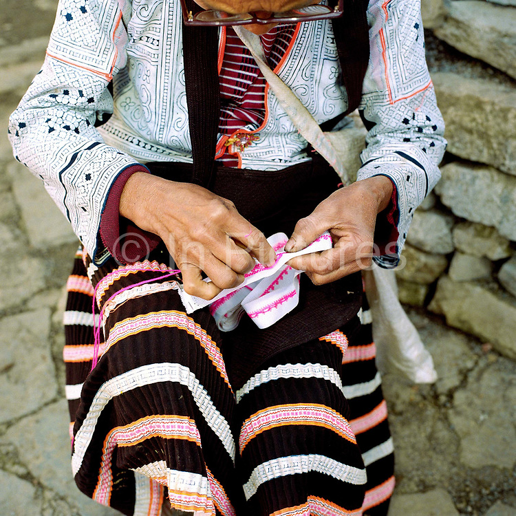 """A Qing Miao (Long Horn Miao) ethnic minority woman wearing her traditional costume sews outside her home in Longga village (Ghao Xin), Guizhou province, China. Almost 35% of Guizhou's population is made up of over 18 different ethnic minorities including the Miao. Each Miao group became isolated in these mountainous regions, hence the present day diversity in their culture, costume and dialects. According to a popular saying, """"if you meet 100 Miaos, you will see 100 costumes."""""""