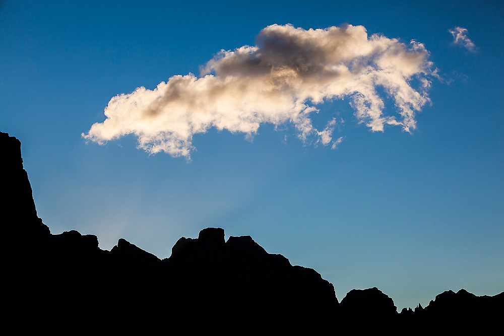 A cloud passes over the silhouette of jagged cliff tops on Moskenesoya, Lofoten Islands, Norway.