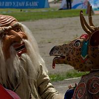 "Buddhist Tsam dancers dressed as Tsagaan Uuvgon (""old white man"") and Buga (the deer) , wait to perform at the national naadam festival in Ulaanbaator, Mongolia."