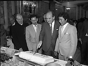 Vietnamese Refugees are Naturalised.  (R61)..1987..08.07.1987..07.08.1987..8th July 1987..A large group of Vietnamese refugees were presented with certificates of naturalisation by Justice Minister, Gerard CollinsTD at the dept of Foreign Affairs in Iveagh House today. The vietnamese were dispossed due to the Vietnam war.The group ,consisting of 156 adults, arrived in Ireland from Vietnam and some refugee camps inHong Kong and Malaysia...Image shows Minister Gerard Collins cutting the celebration cake after the naturalisation ceremony