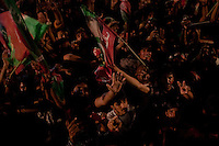 Supporters of Imran Khan, chairman of the Pakistan Tehreek-e-Insaf, cheer and wave party flags as he appears on stage during an election campaign rally in Multan, Pakistan, Monday, May 6, 2013. Pakistan is due to hold a general election on May 11, the first transition of power between democratically elected governments.