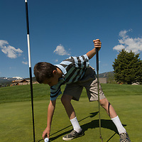 Youngster Eddie Starz picks up his ball by the hole on a green at Big Sky Golf Course in Big Sky, Montana.