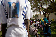 The face of American President Barack Obama is seen on the back of a boy's t-shirt during a gathering of local Darfur women, waiting outside the govenor's compound for a cultural event and sppeches to take place where women from remote parts of Sudan gathered to discuss peace and political issues.