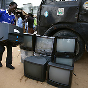 Electronic waste export to Nigeria...Alaba International Market, one of the largest markets for electronic goods in West Africa.  New and old - and a lot of non-working electronic goods such as TVs and computers come in to the market via Lagos harbour from the US, Western Europe and China...Container 4629416 from the UK is being emptied for its load, including the TV tracked by Greenpeace.  Rows of second hand tvs from the container, lost made by Philips...The shipment - TV-set originally delivered to municipality-run collecting point in UK for discarded electronic products - was tracked and monitored by Greenpeace using a combination of GPS (Global Positioning System using satellites), GSM (positioning using data from mobile networks to triangulate approximate positions) and an onboard radiofrequency transmitter (used for making triangulations in combination with handheld directional receivers used by team on ground) is placed inside the TV-set.  The TV arrived in Lagos in container no 4629416.