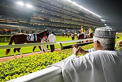 Man at parade ring at horse racing meeting at Al Meydan racecourse at night in Dubai United Arab Emirates