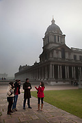 Thick fog over the Royal National Maritime Museum at Greenwich in London making a peaceful yet eerie landscape atmosphere as structures appear and disappear over the River Thames. Modern and old industrial and commercial architecture is releaved through a mist which lasted tthrough the entire day.