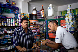 Julio Rodrguez talkes with Victor Marion, a worker at the Maria Leonza pharmacy,  in Petare, one of the largest and most dangerous slums of Caracas.  Pfizer is trying to increase their market share in the slums and are targeting clinics, hospitals and pharmacies, sending sales representatives like Julio to the far reaches of the slum.