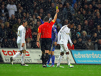 Saturday, 03 November 2012..Pictured: Jonathan De Guzman of Swansea (R) is shown a yellow card by referee K Friend (C)..Re: Barclays Premier League, Swansea City FC v Chelsea at the Liberty Stadium, south Wales.