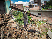 03 AUGUST 2015 - SANKHU, NEPAL:  A laborer hauls corrugated metal used as roofing to a work site where he will rebuild a home destroyed in the earthquake in Sankhu, a community about 90 minutes from central Kathmandu. The home was damaged in the earthquake and the owners hope to rebuild on the site but first half to take down what's left of the existing home. The Nepal Earthquake on April 25, 2015, (also known as the Gorkha earthquake) killed more than 9,000 people and injured more than 23,000. It had a magnitude of 7.8. The epicenter was east of the district of Lamjung, and its hypocenter was at a depth of approximately 15 km (9.3 mi). It was the worst natural disaster to strike Nepal since the 1934 Nepal–Bihar earthquake. The earthquake triggered an avalanche on Mount Everest, killing at least 19. The earthquake also set off an avalanche in the Langtang valley, where 250 people were reported missing. Hundreds of thousands of people were made homeless with entire villages flattened across many districts of the country. Centuries-old buildings were destroyed at UNESCO World Heritage sites in the Kathmandu Valley, including some at the Kathmandu Durbar Square, the Patan Durbar Squar, the Bhaktapur Durbar Square, the Changu Narayan Temple and the Swayambhunath Stupa. Geophysicists and other experts had warned for decades that Nepal was vulnerable to a deadly earthquake, particularly because of its geology, urbanization, and architecture.    PHOTO BY JACK KURTZ