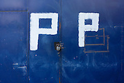 Painted letter Ps on steel gates warning of constant parking in south London.