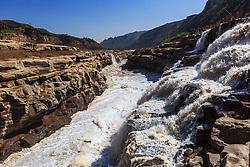April 18, 2018 - Shanxi, Shanxi, China - Shanxi, CHINA-18th April 2018: The Hukou Waterfall is the largest waterfall on the Yellow River, China, the second largest waterfall in China (after the Huangguoshu Waterfall), and the world's largest yellow waterfall. It is located at the intersection of Shanxi Province and Shaanxi Province, 165 km (103 mi) to the west of Fenxi City, and 50 km (31 mi) to the east of Yichuan where the middle reaches of the Yellow River flow through Jinxia Grand Canyon. The width of the waterfall changes with the season, usually 30 metres (98 ft) wide but increasing to 50 m (164 ft) during flood season. It has a height of over 20 m (66 ft). When the Yellow River approaches the Hukou Mountain, blocked by mountains on both sides, its width is abruptly narrowed down to 20 m (66 ft) - 30 m (98 ft). The water's velocity increases, and then plunges over a narrow opening on a cliff, forming a waterfall 15 m (49 ft) high and 20 m (66 ft) wide, as if water were pouring down from a huge teapot. Hence it gets the name Hukou (literally ''flask mouth'') Waterfall. (Credit Image: © SIPA Asia via ZUMA Wire)