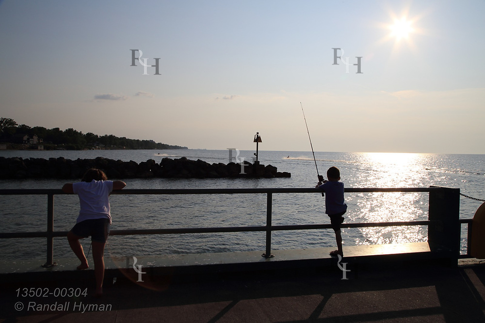 Sun silhouettes kids fishing from Miller Road Park pier on Lake Erie at Avon Lake, OH.