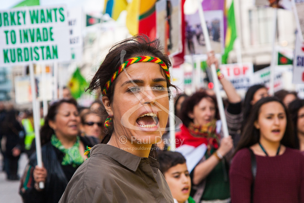 London, October 19th 2014. Hundreds of London's Kurdish community march throgh the capital in protest against ISIS and the Turkish government who they accuse, by not getting involved in military action against ISIS, of using the Jihadists to wipe out Kurds who have long been campaigning for an independent Kurdistan. PICTURED: A woman chants slogans as hundreds of Kurds march on Regents Street.