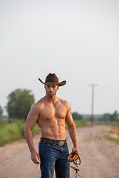 muscular cowboy without a shirt holding reins on a ranch