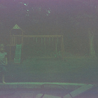 1. When was this photo taken?<br /> <br /> Summer 2005<br /> <br /> 2. Where was this photo taken?<br /> <br /> Pound Ridge, NY<br /> <br /> 3. Who took this photo?<br /> <br /> My 5 year old son<br /> <br /> 4. What are we looking at here?<br /> <br /> This is my daughter when she was two. She's standing on a patio wall we just installed. In the background was our children's play set<br /> <br /> 5. How does this old photo make you feel? <br /> <br /> Disappointed, as I often used to feel when picking up prints at the drugstore! Initially there's a feeling of anticipation dropping the film into the envelope & sending it off!  When I'd pick up my photos two weeks later, they were never as good as I had hoped<br /> <br /> 6. Is this what you expected to see?<br /> <br /> I didn't know what to expect. This photo looks like it'd been improperly exposed, like when the back of the camera was opened before the film was fully rolled back. I didn't expect to see my daughter in the photo because we bought our first digital camera right before she was born & I thought we stopped using our 35mm.<br /> <br /> 7. Does this photo bring back any memories?<br /> <br /> YES! Initially, when I received the old photos, I was so disappointed with the quality, that I didn't look closely at them. After a couple of months, I took a closer look, & even bad photos, can evoke strong feelings & memories. My children are teenagers now, & the days of playing on the swing set have long past. What strikes me most in the picture, though, are my daughter's chubby bare feet! She hates walking outside in bare feet now!<br /> <br /> 8. How do you think others will respond to this photo? <br /> <br /> Because of the poor quality, I think others will barely give it a glance, as was my first inclination. But maybe they too will remember the frustration & limitations of 110 & 35mm film. Today, photos whose quality cannot be enhanced with software, or are not to our liking, are immediately deleted from our