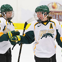 1st year forward Sam Geekie (15) of the Regina Cougars and 5th year defender Krista Metz (4) of the Regina Cougars in action during the Women's Hockey Home Game on October 15 at Co-operators arena. Credit: Arthur Ward/Arthur Images
