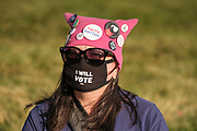 """17 OCTOBER 2020 - DES MOINES, IOWA: A woman wearing a """"pink pussy hat"""" waits for the We Dissent Women's March to start. About 300 women participated in the We Dissent Women's March in Des Moines. The march was one of several held across the US to protest the confirmation of Amy Coney Barrett to the Supreme Court seat once held by Ruth Bader Ginsburg. The women marched through downtown and passed by the closed offices of US Senators Chuck Grassley and Joni Ernst.          PHOTO BY JACK KURTZ"""