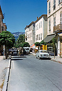 Vehicles traffic on town street historic buildings, Calvi, Corsica, France in late 1950s