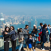 People taking selfie from the Peak with Hong Kong on background