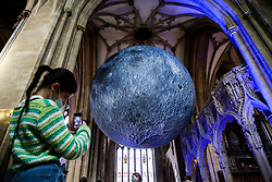 © Licensed to London News Pictures. 15/08/2021. Bristol, UK. A woman takes a photograph of Luke Jeram's Moon installation in Bristol Cathedral. Measuring seven metres in diameter, the Museum of the Moon features detailed NASA imagery of the lunar surface. At an approximate scale of 1:500,000 each centimetre of the internally lit spherical sculpture represents 5 km of the moon's surface. The Museum of the Moon  is open until 30 August 2021. Photo credit: Dinendra Haria/LNP