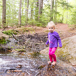 A young girl plays in the woods at the Orris Falls Preserve in South Berwick, Maine.
