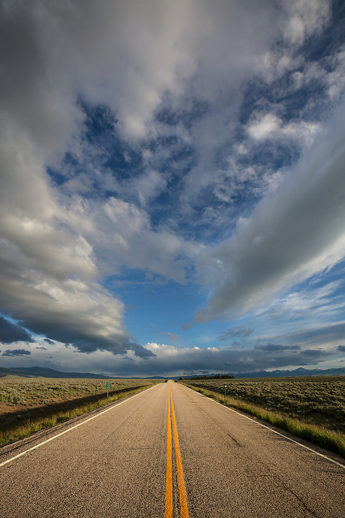 Temporary opening of sunlight along a rural highway in Montana's Big Sky Country in springtime.  Licensing and Open Edition Prints.