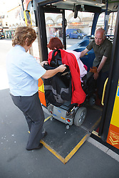 Wheelchair user with cerebral palsy getting off a bus using ramp.