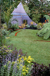General view showing lawn with rill, tropical style planting and large 'shark's fin' dividing structure.