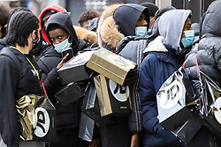 © Licensed to London News Pictures. 02/12/2020. London, UK. Shoppers queue outside a branch of JD Sports on Oxford Street. Today England returns to tiered COVID restrictions following the end of the second national lockdown. Photo credit: George Cracknell Wright/LNP