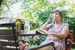 Senior woman drinking water while reading a book in the garden, Altoetting, Bavaria, Germany